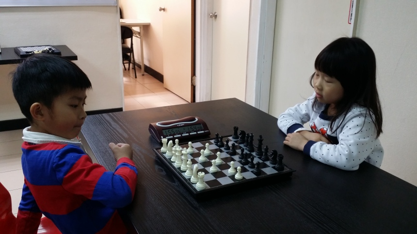 Brother and sister learn chess together